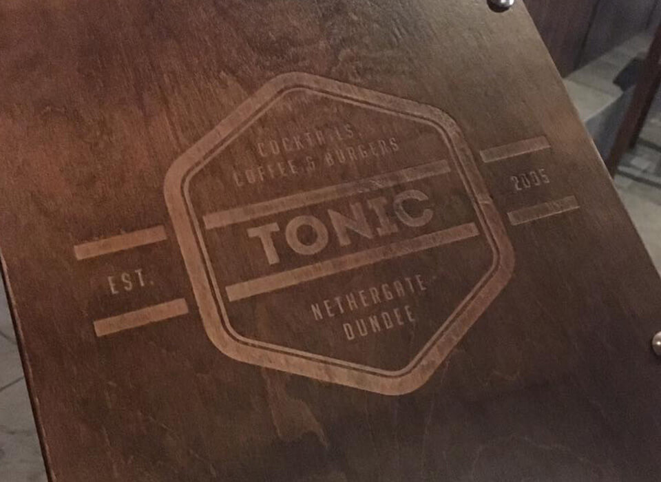 Photograph showing the Tonic logo laser etched into a wooden board